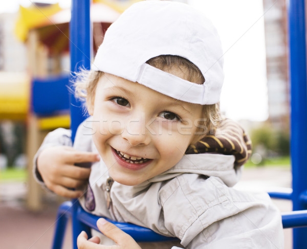 little cute real boy playing on playground, hanging on gymnastic ring cheerful Stock photo © iordani