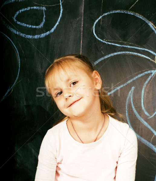 little cute girl in classroom at blackboard writing smiling, preschooler from back alone, lifestyle  Stock photo © iordani