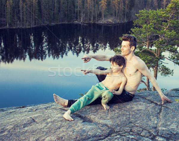middle age man with little cute son doing sport yoga on the top of the mountain together, happy fami Stock photo © iordani