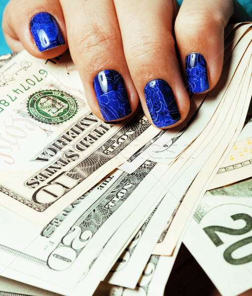 close up fingers with deep blue creative pattern manicure holding dollars Stock photo © iordani