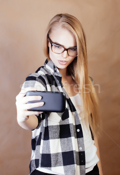 young pretty blond hipster girl making selfie on warm brown background, lifestyle people concept Stock photo © iordani