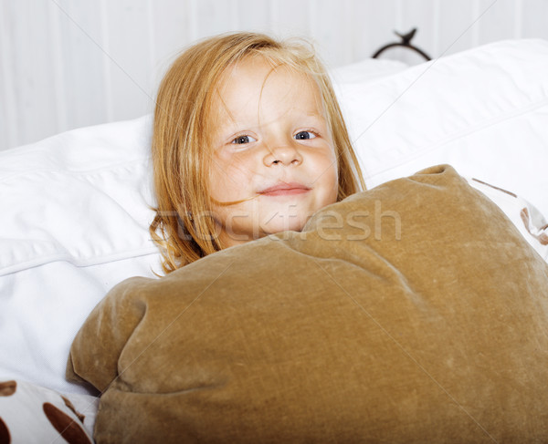 little cute blonde norwegian girl playing on sofa with pillows, lifestyle people concept Stock photo © iordani