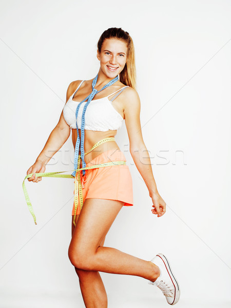 woman measuring waist with tape on knot like a gift, tan isolated close up white background Stock photo © iordani
