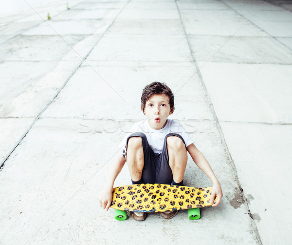 little cute boy with skateboard on playground alone training, copyspace, lifestyle people concept Stock photo © iordani