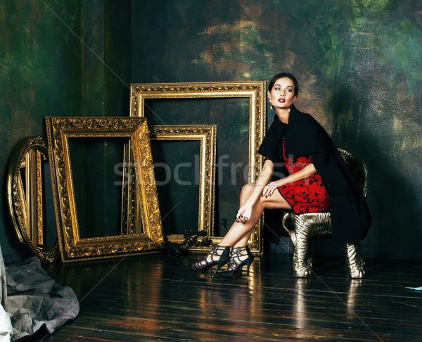 beauty rich brunette woman in luxury interior near empty frames, wearing fashion clothes, lifestyle  Stock photo © iordani