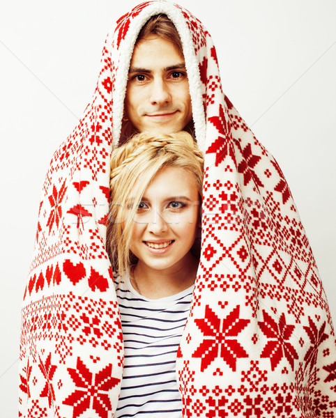 young pretty teenage couple at Christmas time warming in red decorated blanket, hipster guy with his Stock photo © iordani