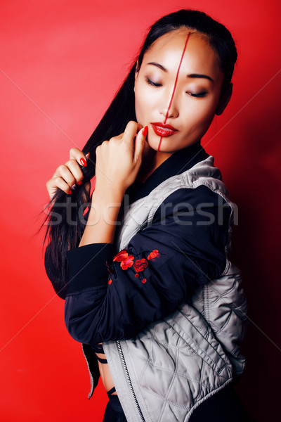 young pretty asian girl posing cheerful on red background, fashion style makeup and hair, lifestyle  Stock photo © iordani