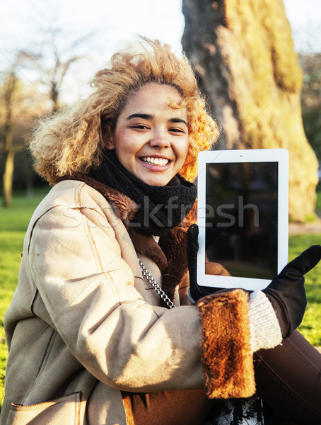 Stock photo: young cute blond african american girl student holding tablet and smiling, lifestyle people concept
