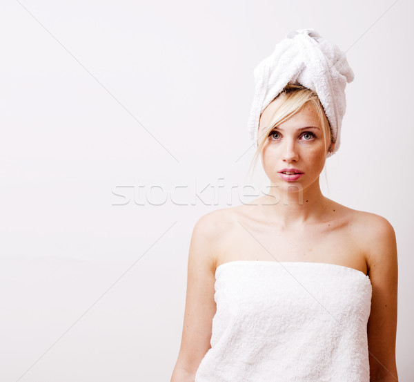 young pretty blond woman in towel after shower posing on white background with copyspace, lifestyle  Stock photo © iordani