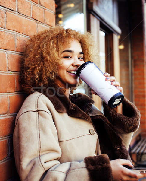 young pretty african american women drinking coffee outside in cafe, modern real business woman life Stock photo © iordani