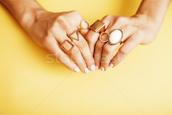 woman hands with manicure and jewelry ring on yellow background, beauty style concept Stock photo © iordani