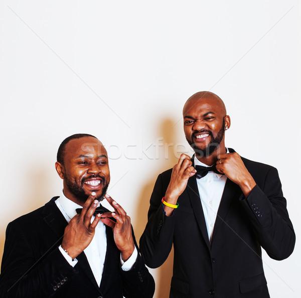 two afro-american businessmen in black suits emotional posing, gesturing, smiling. wearing bow-ties  Stock photo © iordani