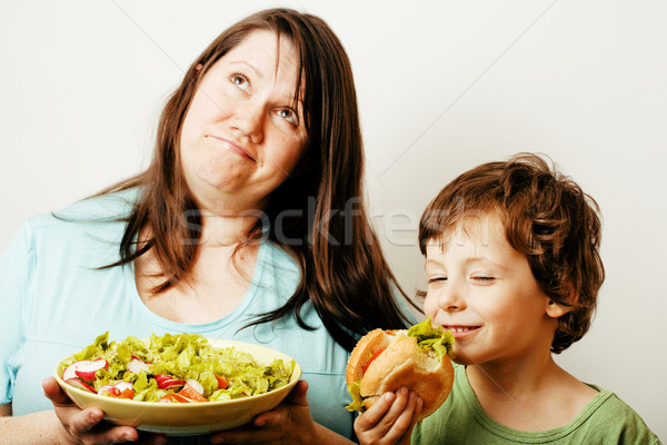 mature woman holding salad and little cute boy with hamburger te Stock photo © iordani