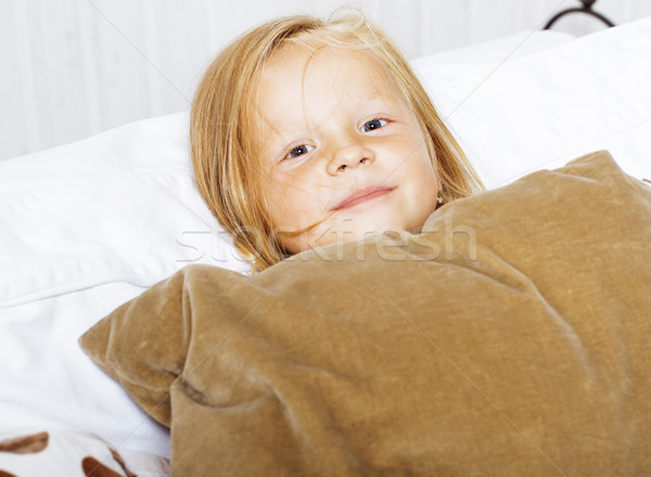 little cute blonde norwegian girl playing on sofa with pillows,  Stock photo © iordani