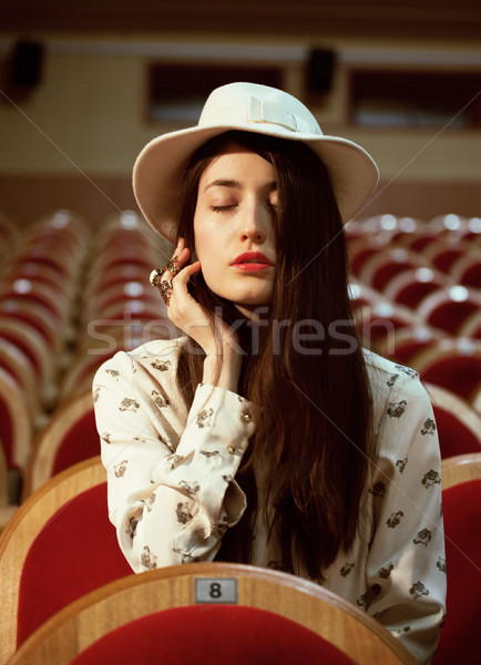 portrait of a pretty girl hipster in a movie theater wearing hat, dreaming alone Stock photo © iordani
