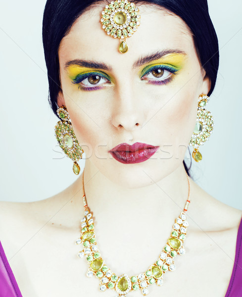 young pretty caucasian woman like indian in ethnic jewelry close up on white, bridal bright makeup Stock photo © iordani