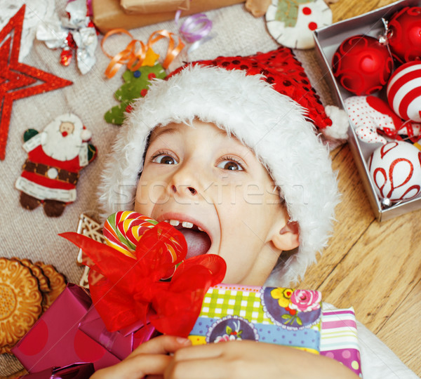 little cute boy with Christmas gifts at home. close up emotional happy smiling in mess with toys, li Stock photo © iordani