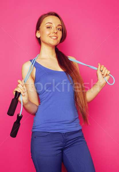 young happy slim girl with skipping rope on pink background smiling sweety cute Stock photo © iordani