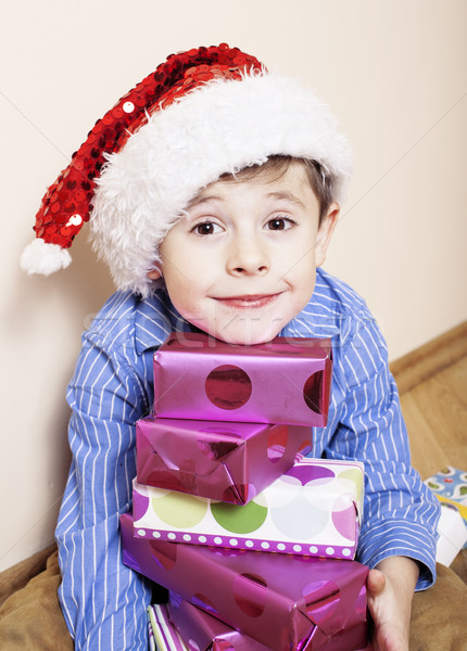 little cute boy with Christmas gifts at home. close up emotional face on boxes in santas red hat Stock photo © iordani