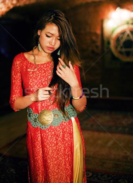 young pretty asian girl in bright colored interior on carpet view Stock photo © iordani
