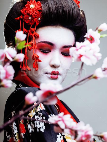 young pretty geisha in kimono with sakura and red decoration design on white background Stock photo © iordani