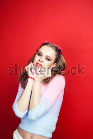 young pretty teenage girl on bright red background, happy smilin Stock photo © iordani