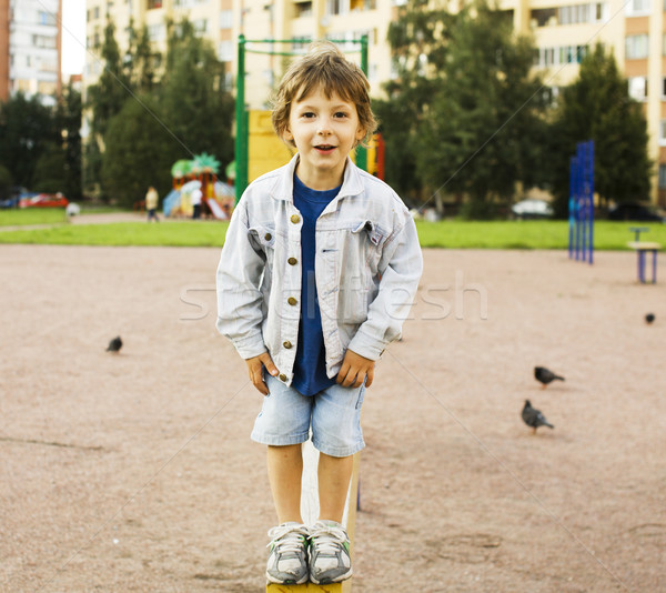 little cute boy playing on playground, hanging on gymnastic ring Stock photo © iordani