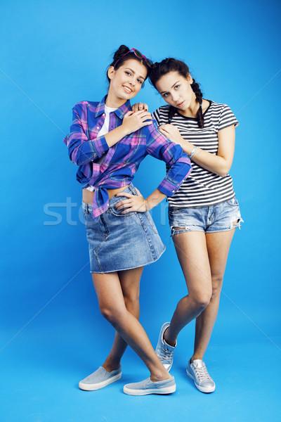Stock photo: best friends teenage girls together having fun, posing emotional on blue background, besties happy s
