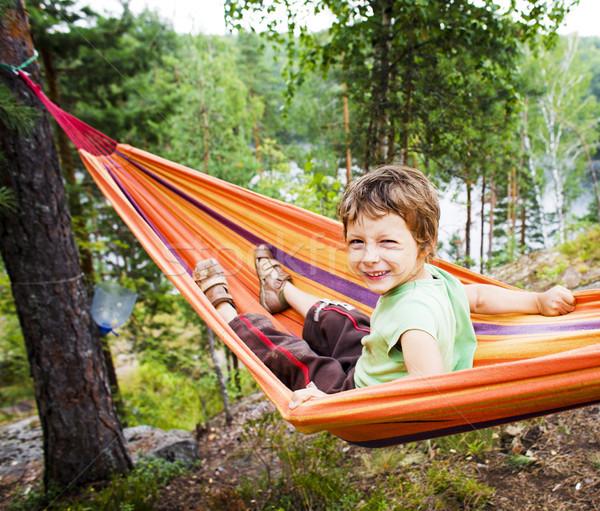 Kicsi aranyos fiú függőágy mosolyog erdő Stock fotó © iordani