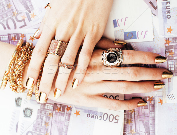 hands of rich woman with golden manicure and many jewelry rings on cash euros Stock photo © iordani