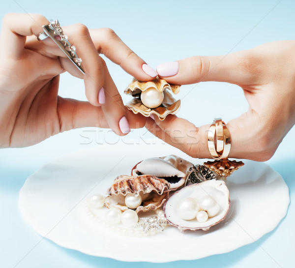 beautiful woman hands with pink manicure holding plate with pearls and sea shells, luxury jewelry co Stock photo © iordani