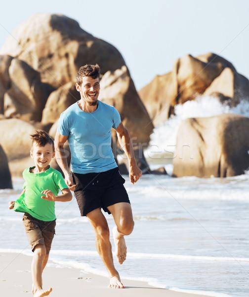 happy family on beach playing, father with son walking sea coast Stock photo © iordani