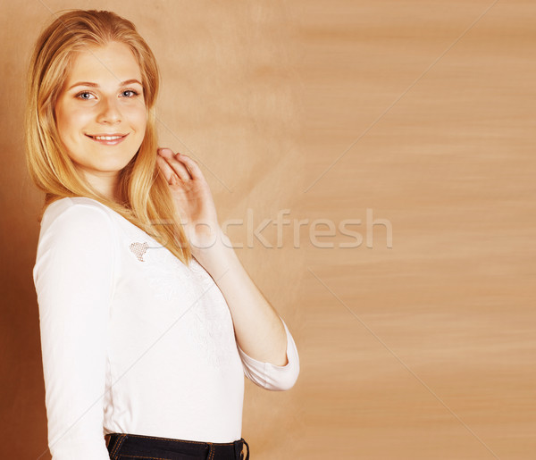 young pretty blond woman happy cheerful smiling closeup on warm brown background, lifestyle real peo Stock photo © iordani