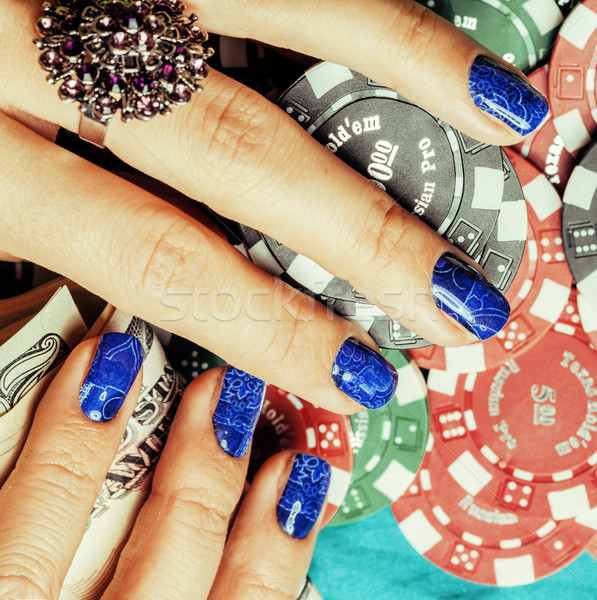 hands of young caucasian woman with blue manicure at casino tabl Stock photo © iordani
