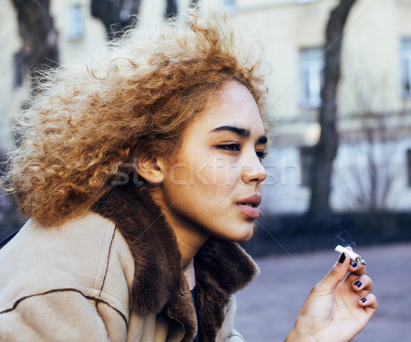 young pretty girl teenage outside smoking cigarette, looking lik Stock photo © iordani