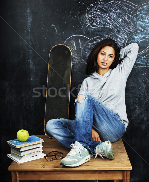 young cute teenage girl in classroom at blackboard seating on table smiling Stock photo © iordani
