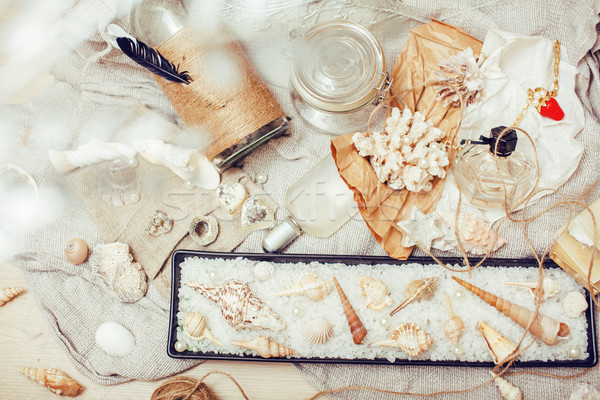 Stock photo: a lot of sea theme in mess like shells, candles, perfume, girl stuff on linen, pretty textured post