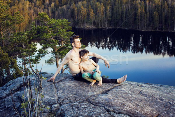 Stock photo: middle age man with little cute son doing sport yoga on the top of the mountain together, happy fami