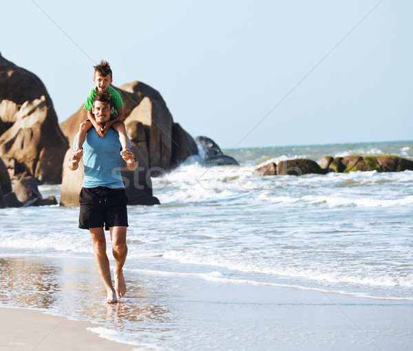 happy family on beach playing, father with son walking sea coast, rocks behind smiling enjoy summer Stock photo © iordani