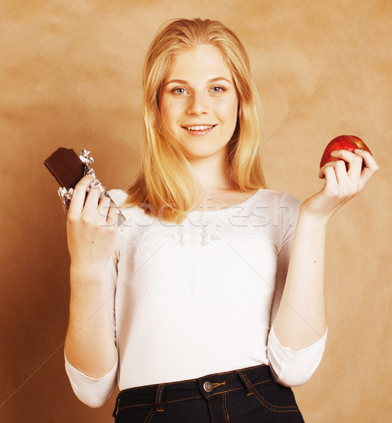 young beauty blond teenage girl eating chocolate smiling, choice Stock photo © iordani