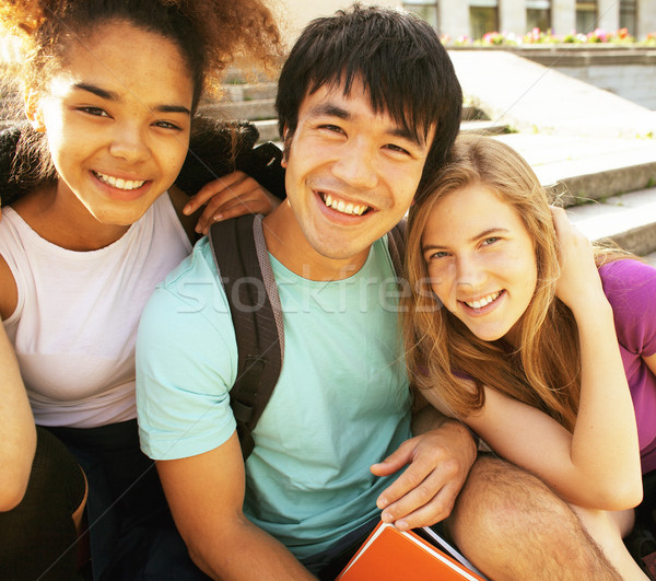cute group of teenages at the building of university with books huggings, back to school Stock photo © iordani