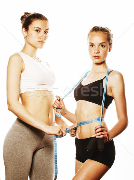 two sport girls measuring themselves isolated on white Stock photo © iordani