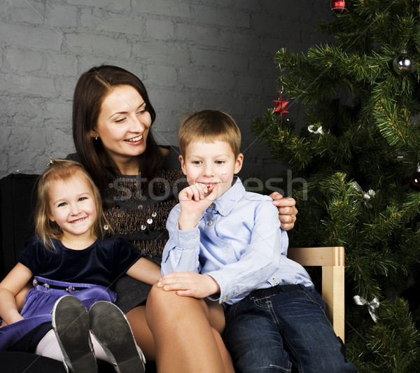 portrait of happy family, mother with children seating near Christmas tree, lifestyle people concept Stock photo © iordani