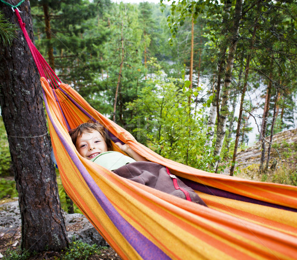 little cute real boy in hammock smiling against landscape with forest and lake hight on mountain, li Stock photo © iordani