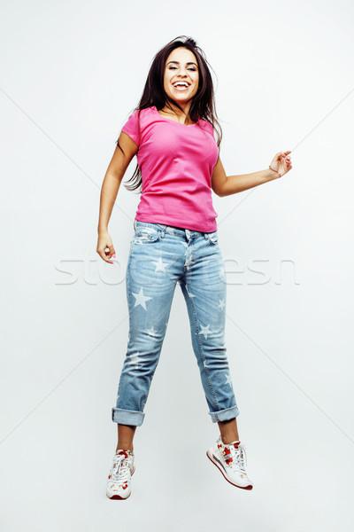 young happy smiling latin american teenage girl emotional posing on white background, jumping flying Stock photo © iordani