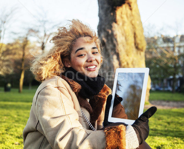 young cute blond african american girl student holding tablet and smiling, lifestyle people concept  Stock photo © iordani