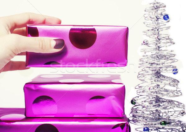 woman manicured hand puting christmas gift to rest pile of purple gifts close up isolated silver lit Stock photo © iordani