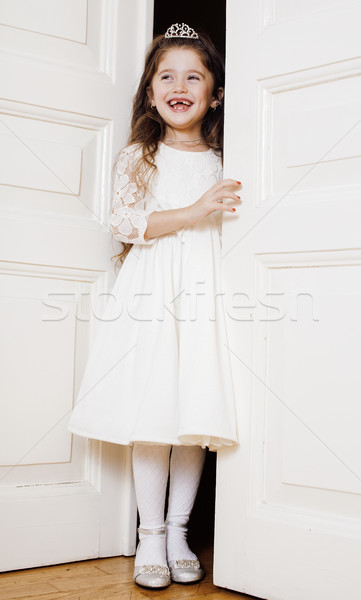 little cute girl at home, opening door well-dressed in white dress, adorable milk fairy teeth, curio Stock photo © iordani