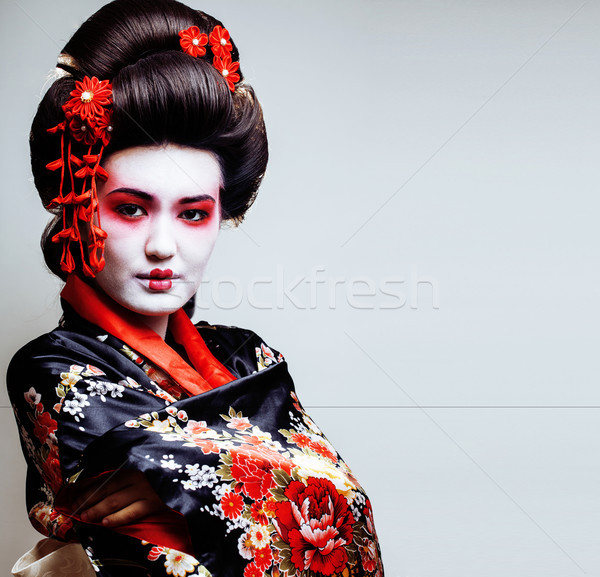 Stock photo: young pretty geisha in kimono with sakura and red decoration des
