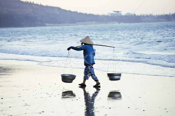 vietnam woman in vietnamese hat walking on seacost at sunset Stock photo © iordani